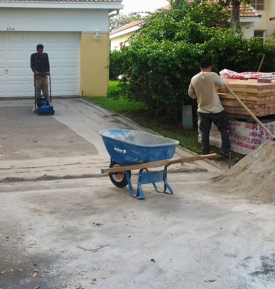 people with sandand pavers on a driveway