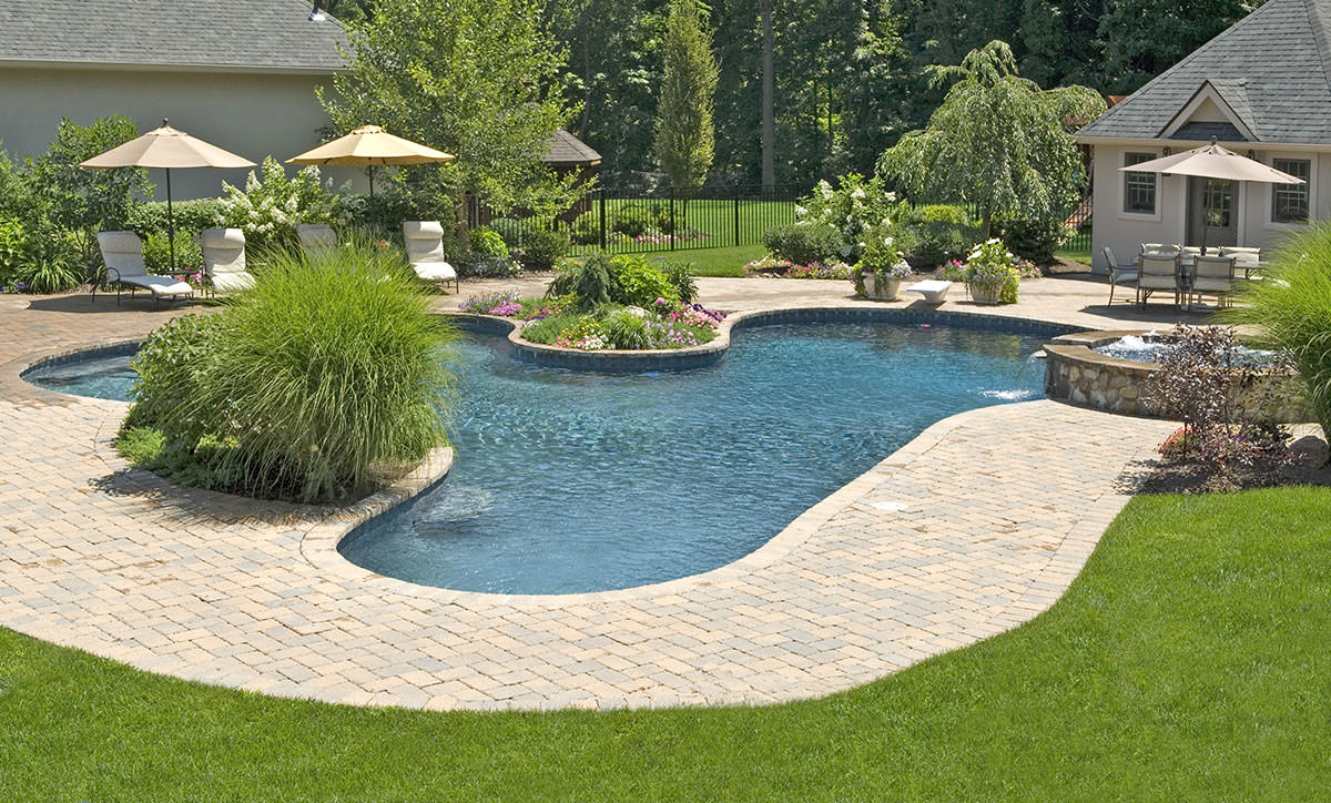 big pool deck with travertine and a backyard